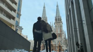 Couple hugs each other and looking on the church
