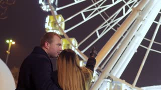 Couple of in love people enjoys a beautiful ferris wheel