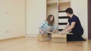 Couple pack things into box for relocation from house