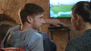 Couple watching a football match on TV together