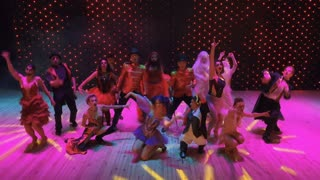 Crazy people dances in colorful lights at stage in modern theatre