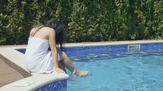 Curly brunette in bathrobe sits near blue pool and splashes water