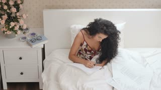 Curly brunette writes a letter in the bed