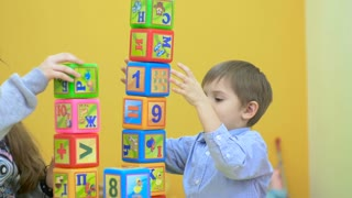 Cute boy and pretty girl playing with cubes in children's room