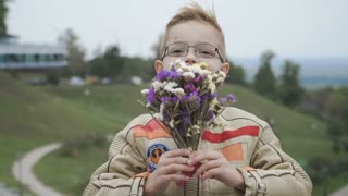 Cute boy presents flowers to the camera in slowmotion
