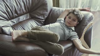 Cute boy relax on armchair