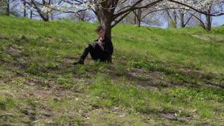 Cute boys writes poem sitting under flower tree on grass in park