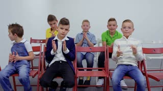 Cute caucasian boys sits at chairs and applauding