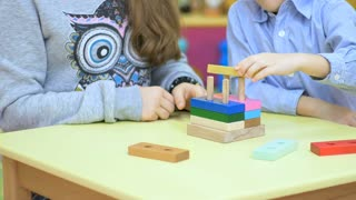 Cute children playing with wooden toys on the table