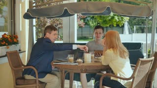 Cute family sits at the terrace of their house and drinks coffee