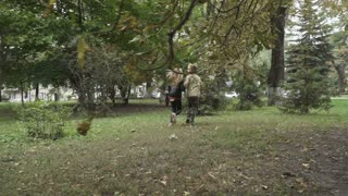 Cute girl and adorable boy holds hands and running in park in slowmotion
