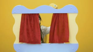 Cute girl playing with toy behind the screen of puppet show