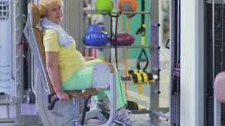 Cute granny trains her legs in the gym on training apparatus