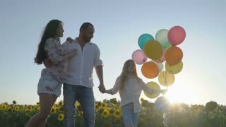 Cute happy family walking with balloons at the sunflower field