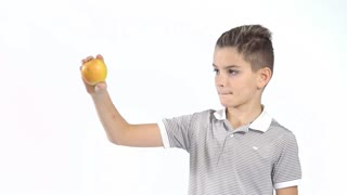 Cute little boy eats apple at white background