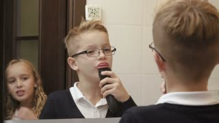 Cute little boy imitates shaving a beard with electric razor