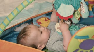Cute little boy lays in children's tent and playing with soft toys