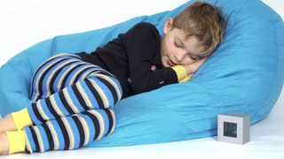 Cute little boy looks on time on clock during sleeping
