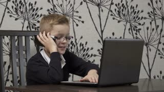 Cute little boy with laptop and phone