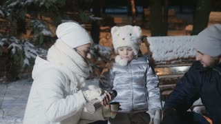 Cute little girl drinks a tea from thermos with family in evening winter park