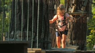 Cute little girl is overcoming obstacles in rope park