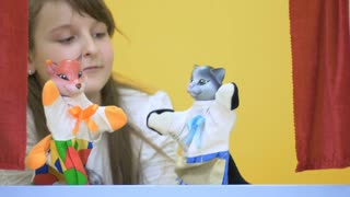 Cute little girl playing with soft toys in puppet show