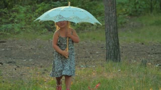 Cute little girl with umbrella walk in forest