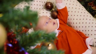 Cute newborn baby girl lies in crib near Christmas tree
