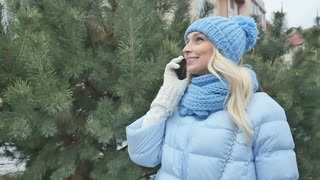 Cute smiling blonde talks on the phone outdoors near the fir-tree