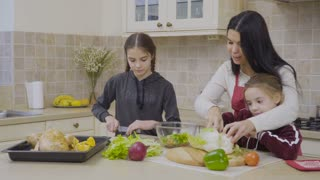 Daughters help mother to cook the dinner