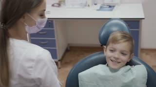 Dentist check the condition of teeth of little boy with angular probe and mirror