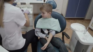 Dentist makes anesthetic injection to a little boy