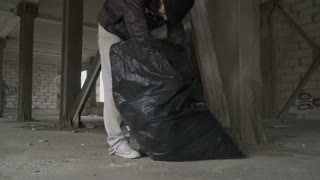 Dirty bum searches something in garbage bag