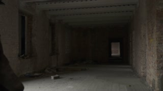 Dirty homeless with garbage bag walks in abandoned building