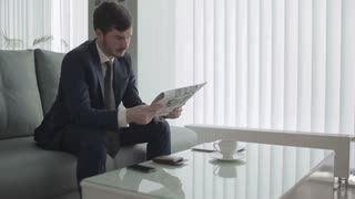 Disapointed businessman waits the boarding on the plane in a vip lounge hall