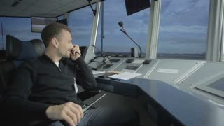 Dispatcher control the airplanes in control tower in airport with portable radio