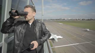 Dispatcher looks after air-traffic with binoculars in control tower of airport