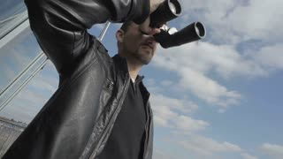 Dispatcher of airport with binoculars against sky