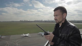 Dispatcher use binoculars to control the air-traffic at the airport