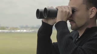 Dispatcher with binoculars controls air-traffic in the control tower