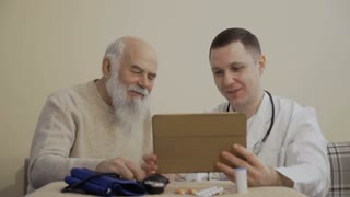 Doctor and old man uses digital tablet sitting at the table