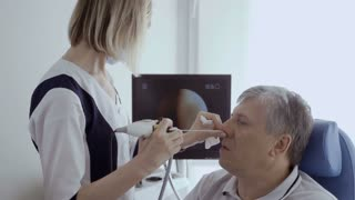 Doctor check nose of elderly man with ENT telescope