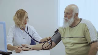 Doctor check pulse of old man with tonometer and stethoscope