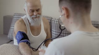 Doctor check pulse of old man with tonometer