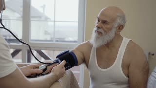 Doctor check pulse of senior man with tonometer