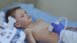 Doctor check the abdomen of little boy with medical ultrasound