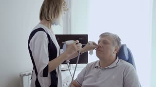 Doctor examine nose od adult man with ENT telescope