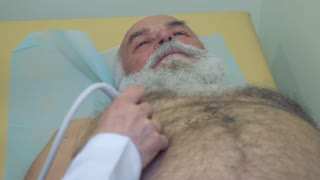 Doctor examining abdomen of senior man with ultrasonography equipment