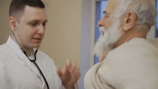 Doctor listens heart of senior man with stethoscope