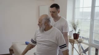 Doctor makes sport exercise with old man